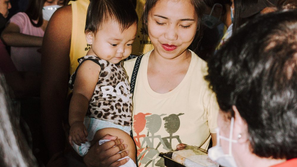 A Taal evacuee receives a packed meal from BAVI