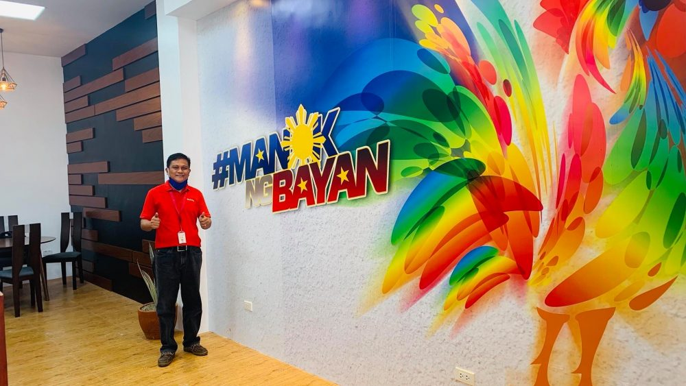 Isabela Business Center head Ronald Nolasco posed in front of a colorful mural at their renovated office